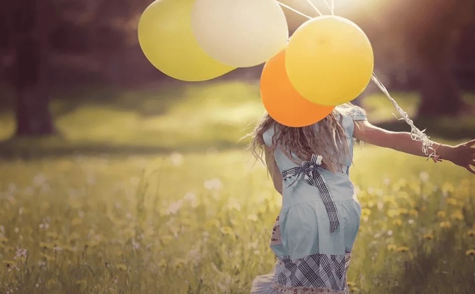На фото изображена девушка с шариками, которая бежит по полю.