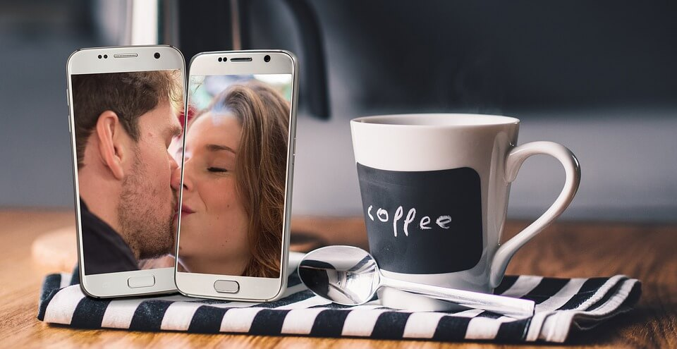 На фото изображено два экрана смартфона, на которых пара влюбленных целуется.