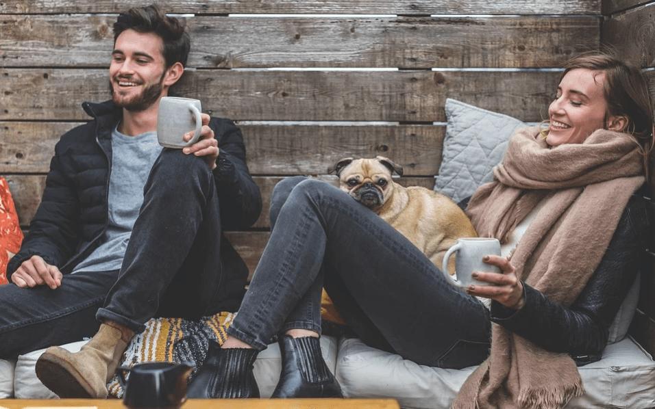 На фото изображена пара, сидящая с чашками и псом на руках.