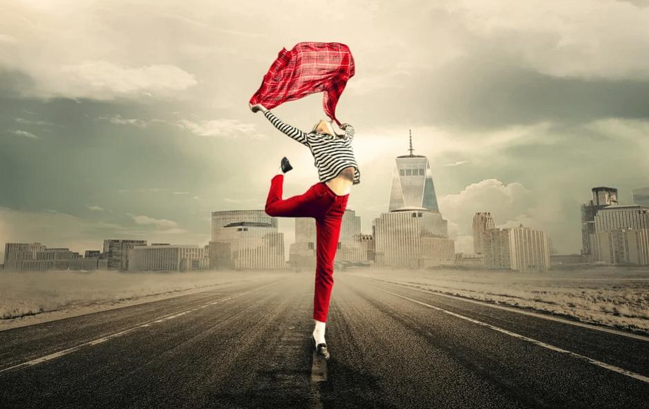 На фото изображена девушка, которая танцует на фоне города.