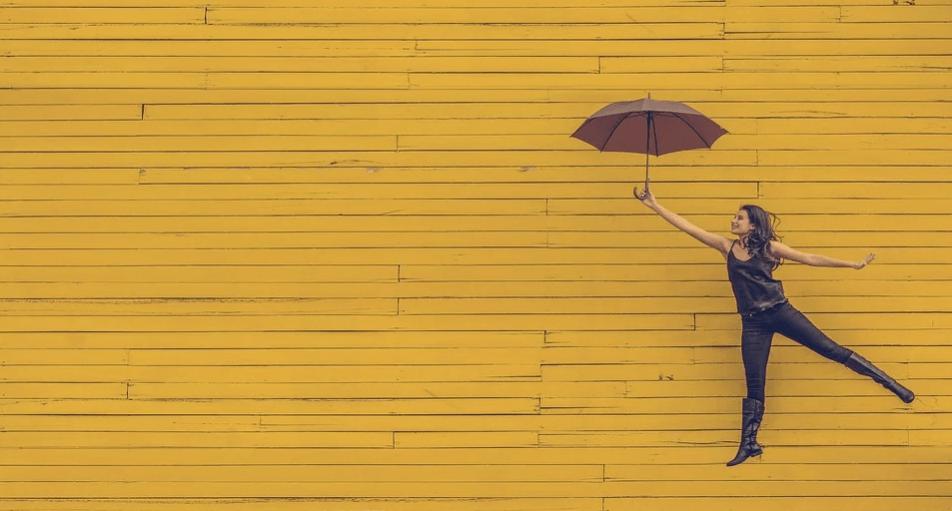 На фото изображена женщина парящая с зонтиком на желтом фоне.