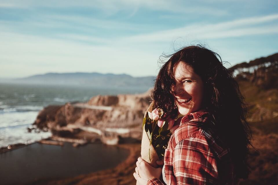 На фото изображена девушка на берегу, с цветами и улыбкой.