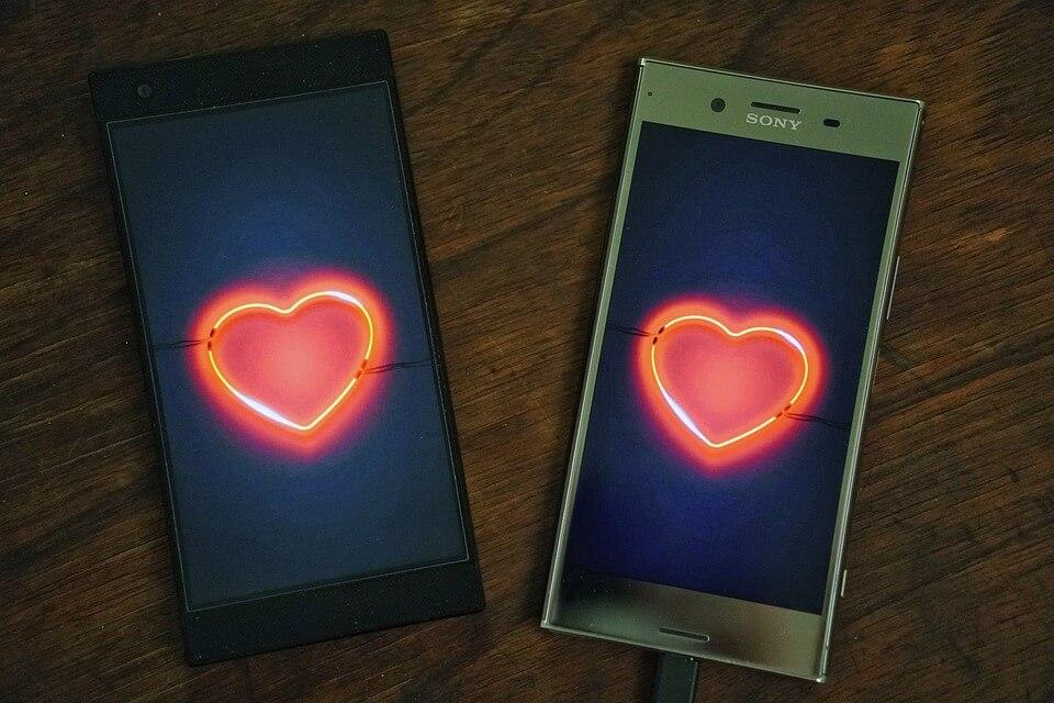 На фото изображены два телефона, на экране которых светятся сердца.