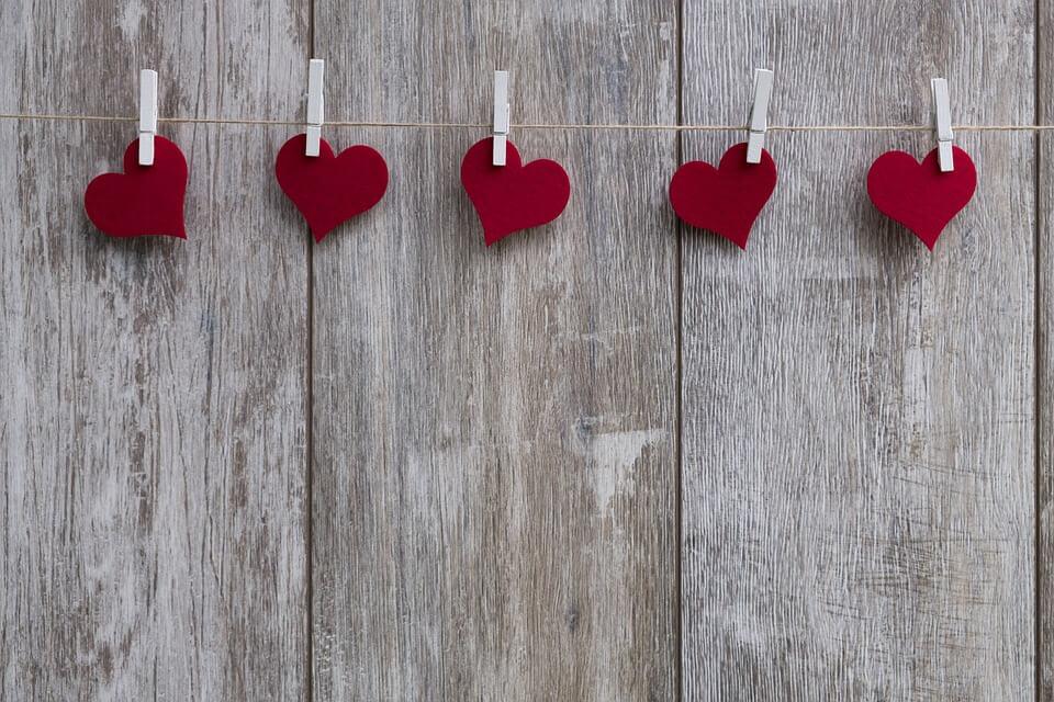 На фото изображены сердечки на прищепках на веревке.