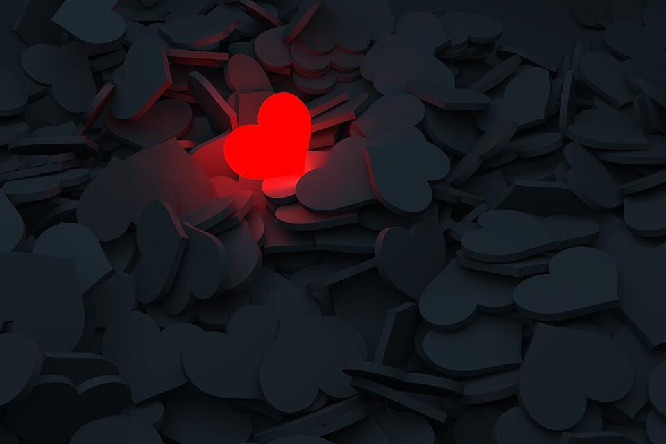 На фото изображено красное сердце в куче черных.