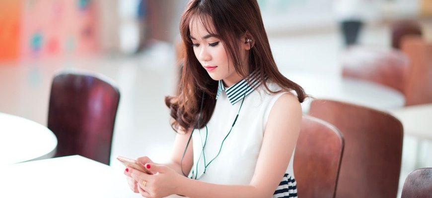 Девушка с телефоном в наушниках. Где найти статусы на корейском языке.