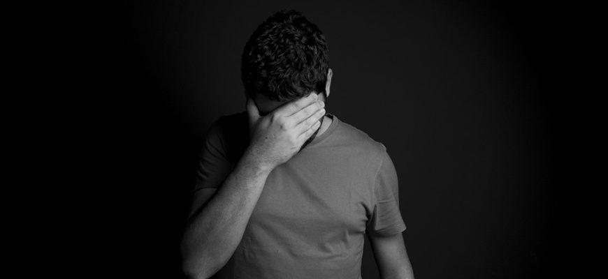 Мужчина закрывает лицо рукой. Где найти статусы про депрессию.