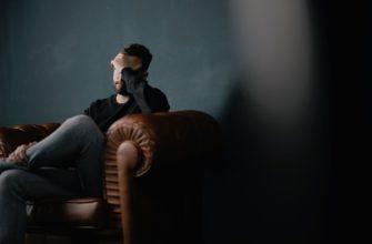 Мужчина на диване держится за голову. Какие есть статусы о разочаровании в человеке.